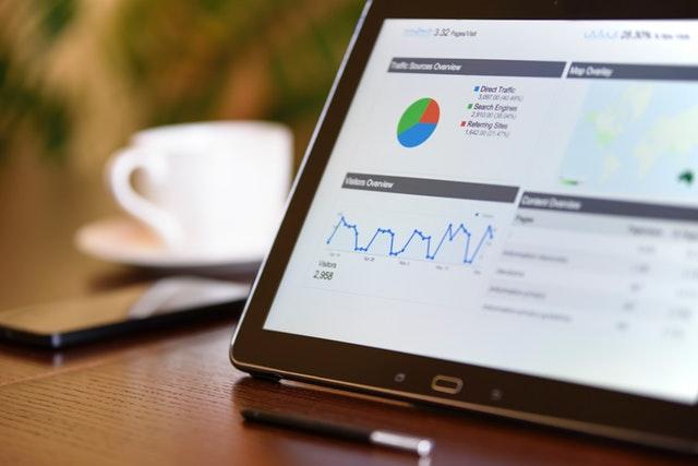notebook s otevřenou stránkou grafů na stole, na kterém je i mobil a hrnek.jpg
